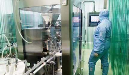 Man stood in cleanroom testing environment wearing blue suit