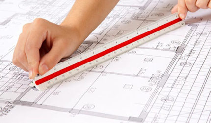 Hand holding ruler over plans