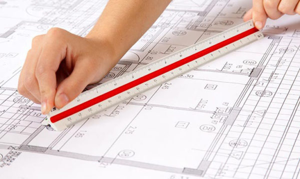 Hand holding ruler over plans for soundproofing party walls