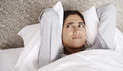 Woman trying to sleep holding pillows over ears and shouting
