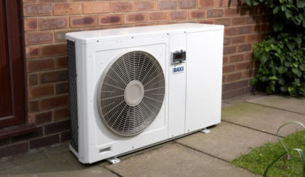 Air source heat pump stood outside house