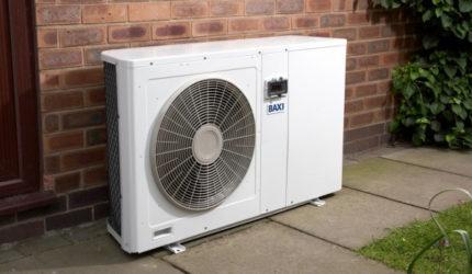 Air source heat pump stood outside house